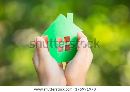 Little paper house in children`s hands against green spring background. Shallow depth of field - stock photo