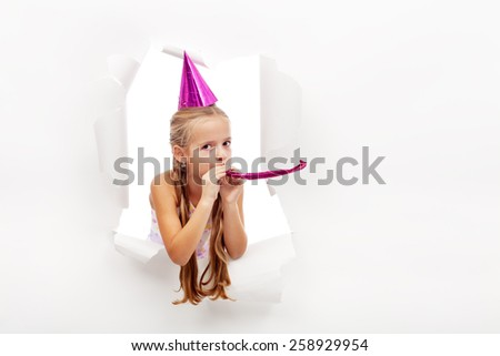 Little party girl with hat and whistle looking out on blast hole in paper - with copy space - stock photo
