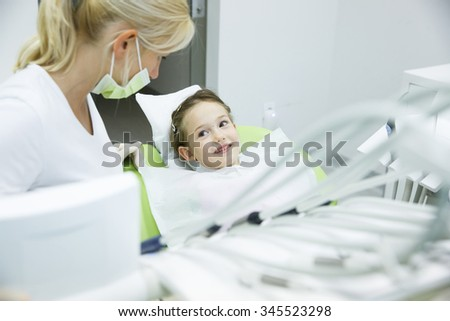Little patient conversing with her dentist at dental office before her regular checkup for caries and gum disease. Early prevention, oral hygiene and milk teeth care concept.  - stock photo