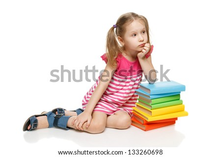 Little pensive girl sitting on the floor leaning on the stack of books looking away at blank copy space, over white background - stock photo