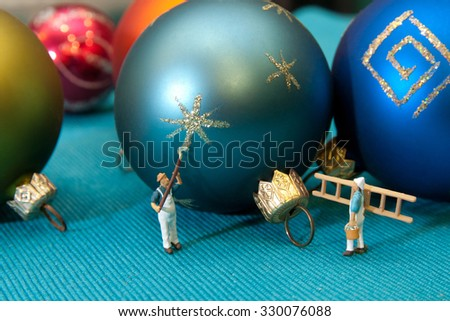 Little people paint Christmas bauble. The concept of teamwork. - stock photo