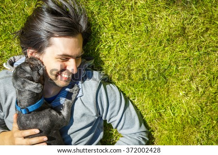Little Pet Dog and His Owner Having Fun Outdoors - stock photo