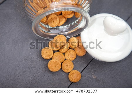 Little pile of tradtional Dutch candy pepernoten with glass jar and heart cover on black wooden background