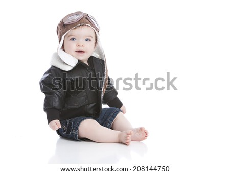 Little pilot.  Adorable baby boy dressed in a pilot hat with goggles and wearing a leather bomber jacket.  Isolated on white with room for your text.  - stock photo