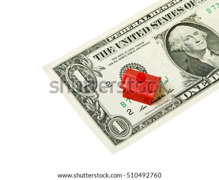 Little plastic red house on a one US dollar banknote isolated on white background.