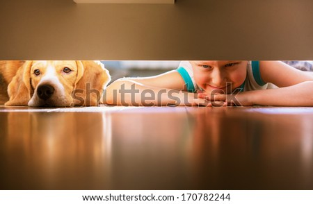 Little prank partners - boy with doggy friend looks under the bed - stock photo