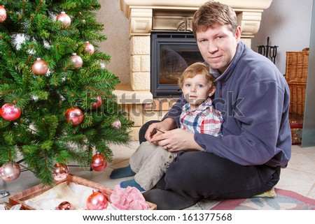 Little preschool boy and his father decorating christmas tree at home with chimney - stock photo