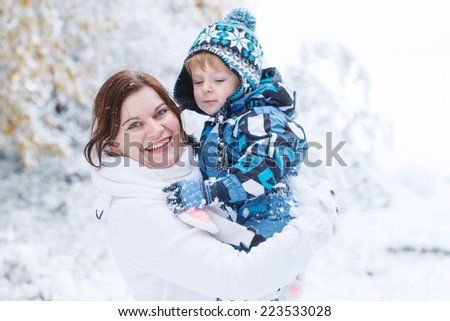 Little preschool boy and his mother playing with first snow in park - stock photo