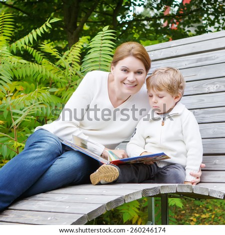 Little preschool boy and his mother sitting on bench in park and reading fairytale book together. Family spending time with reading. - stock photo