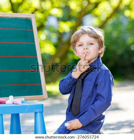 Little preschool boy at blackboard practicing writing letters and mathematics, outdoor school or nursery. Kid learning and schoolboy concept. On summer sunny day. Back to school.