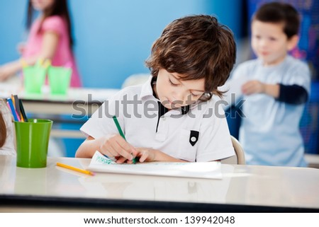 Little preschool boy drawing with sketch pen at desk in kindergarten