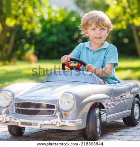 Little preschool boy driving big toy car and having fun, outdoors. - stock photo