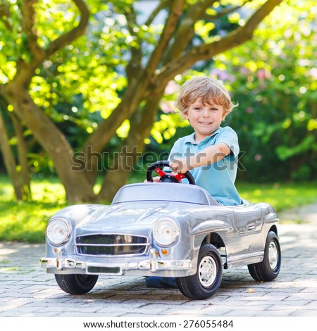 Little preschool boy driving big toy old vintage car and having fun, outdoors. Active leisure with kids on warm summer day. - stock photo