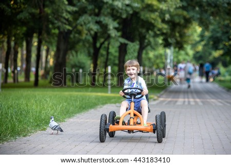 Little preschool boy driving big toy sports car and having fun, outdoors. Active leisure with kids on warm summer day or evening.