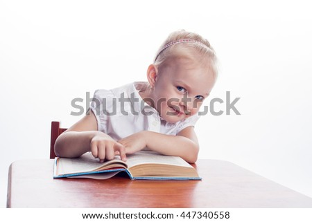Little preschool girl read book, sitting at the table isolated on white background - stock photo
