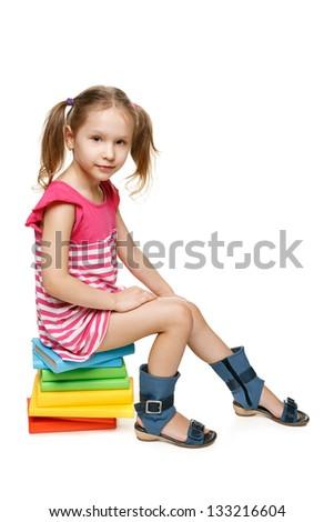 Little preschool girl sitting on the stack of books, in full length, over white background - stock photo