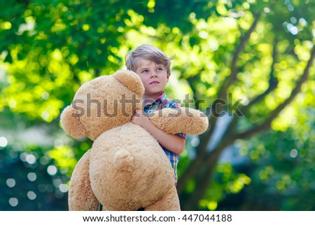 Little preschool kid boy playing with his big plush toy bear, outdoors. Child enjoying warm summer day in nature landscape - stock photo