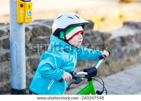 Little preschool kid boy riding with his first green bike in the city. Happy child in colorful clothes standing and waiting near traffic lights. Active leisure for kids outdoors. - stock photo