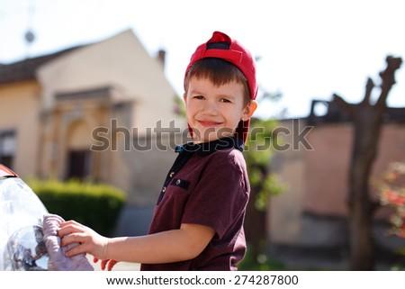 Little preschooler boy wash car outdoor, cleaning - stock photo