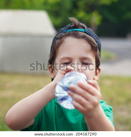 Little preschooler caucasian boy in cap drink outdoor - stock photo