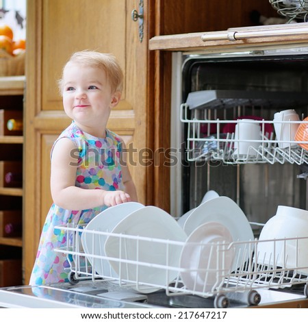Little preschooler child, cute blonde toddler girl helping in the kitchen taking plates out of dish washing machine