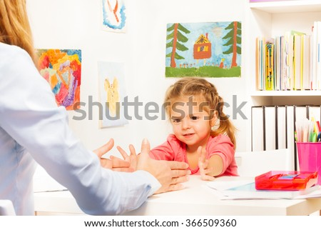Little preschooler doing finger exercises at table - stock photo