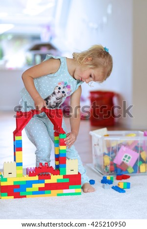 Little preschooler girl building house from plastic blocks. Lovely laughing child, blonde girl of preschool age playing with colorful bricks sitting on carpet in a sunny room at home or kindergarten - stock photo