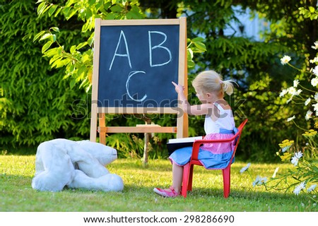 Little preschooler girl excited to go back to school. Cute toddler playing teacher role game outdoors. Happy kid leaning letters and number at kindergarten. Children education concept.  - stock photo