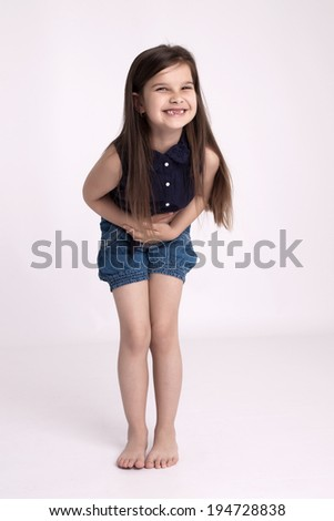 Little preschooler girl in denim shorts and a blue shirt is holding belly and a lot of laughs - stock photo