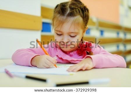 little preschooler girl is drawing in kindergarten - stock photo