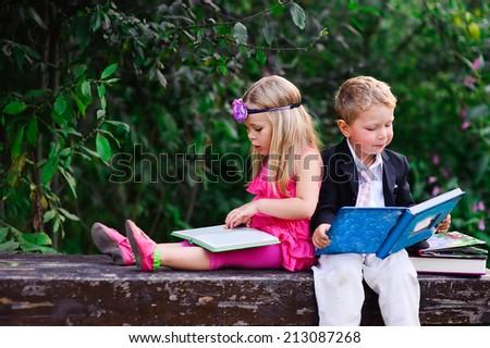 Little preschooler kid reading outdoor - stock photo