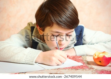 little preteen boy do his homework with bitten apple - stock photo