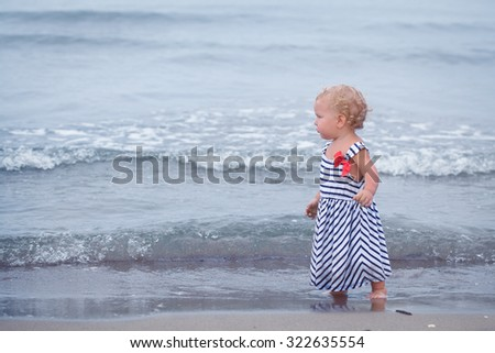 Little pretty baby girl walking on sand by sea, italy,