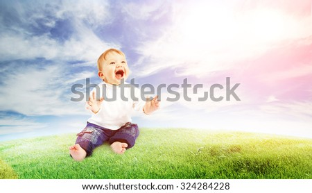 little pretty baby playing in the meadow - stock photo
