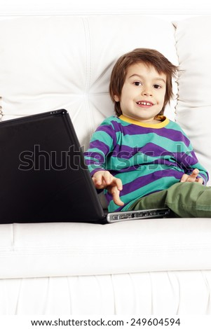Little pretty boy sitting on the sofa with notebook