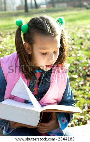 little pretty child reading the book in the park