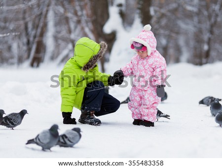 Little pretty girl and boy feed birds in winter snow park, outdoor - stock photo