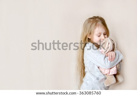 Little pretty girl hugging her toy rabbit and hiding her face with embarrassment or shame or modesty, eyes closed - stock photo
