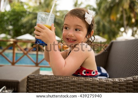 Little pretty girl in a chair at the swimming pool and drinking fresh orange juice. Cute kid smiling happily and enjoying her summer vacation in tropical resort. Healthy lifestyle - stock photo