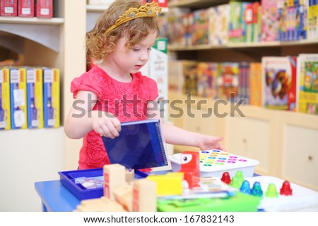 Little pretty girl in crown of princess plays with toys in store.