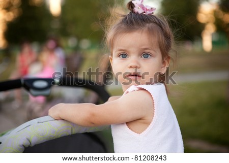 little pretty girl in front of the carriage rolls - stock photo
