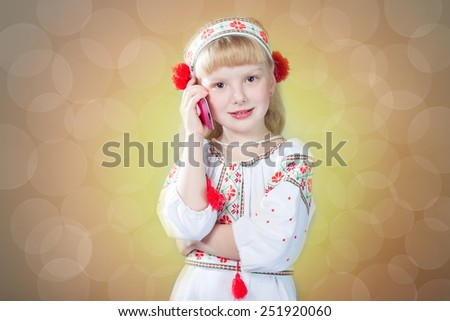 Little pretty girl in handmade embroidered clothes talking on mobile phone
