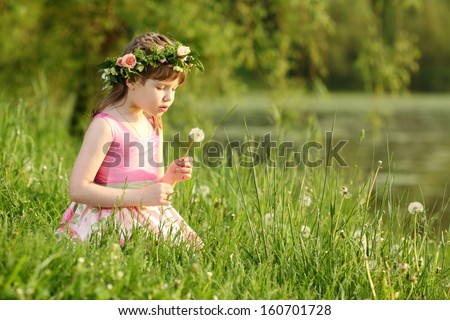 Little pretty girl in pink sits and blows on dandelion on green grass in summer park.