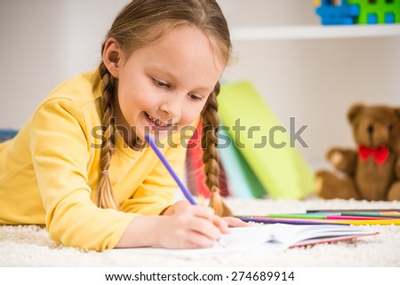 Little pretty  girl in yellow  pullover  laying on carpet and drawing.