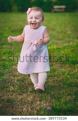 little pretty girl running through the grass and smiles, joy, mischief, childhood - stock photo