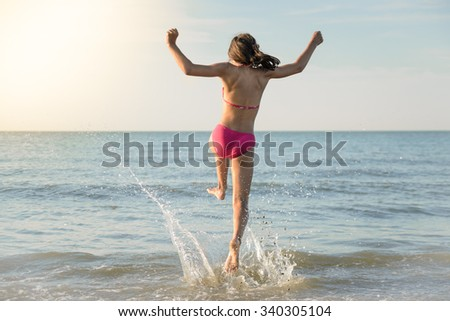 Little pretty girl running to the sea, jumping in the water. Sunny beach by North Sea. - stock photo