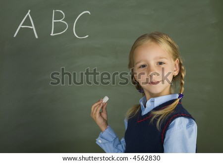 Little, pretty girl standing in front of blackboard. Holding chalk. Smiling and looking at camera - stock photo