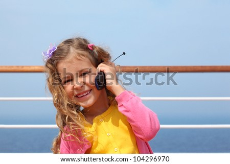 Little pretty girl stands on board ship and says by portable radio - stock photo
