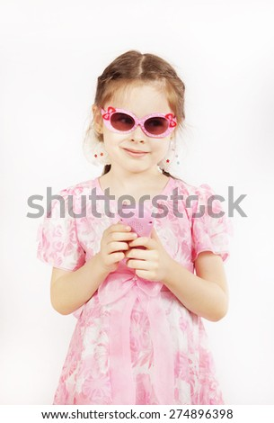 Little pretty girl wearing beautiful pink dress with toy mobile - stock photo