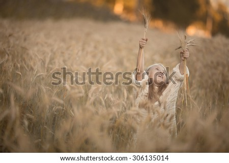 little pretty girl with long blond hair standing in the field of wheat of corn with her hands up to the sun at summer time at sunset - stock photo
